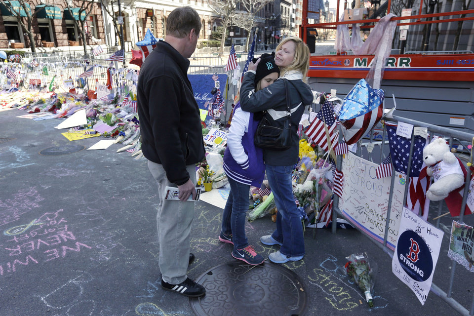 Photo - Holly Holland, right, hugs her daughter Katie, center, as her husband Kevin Holland, left, all of St. Louis,  looks while visiting a makeshift memorial in Boston, Monday, April 22, 2013. The memorial sits on Boylston St., not far from where two bombs exploded near the finish line of the Boston Marathon, Monday, April 15, 2013. (AP Photo/Steven Senne)