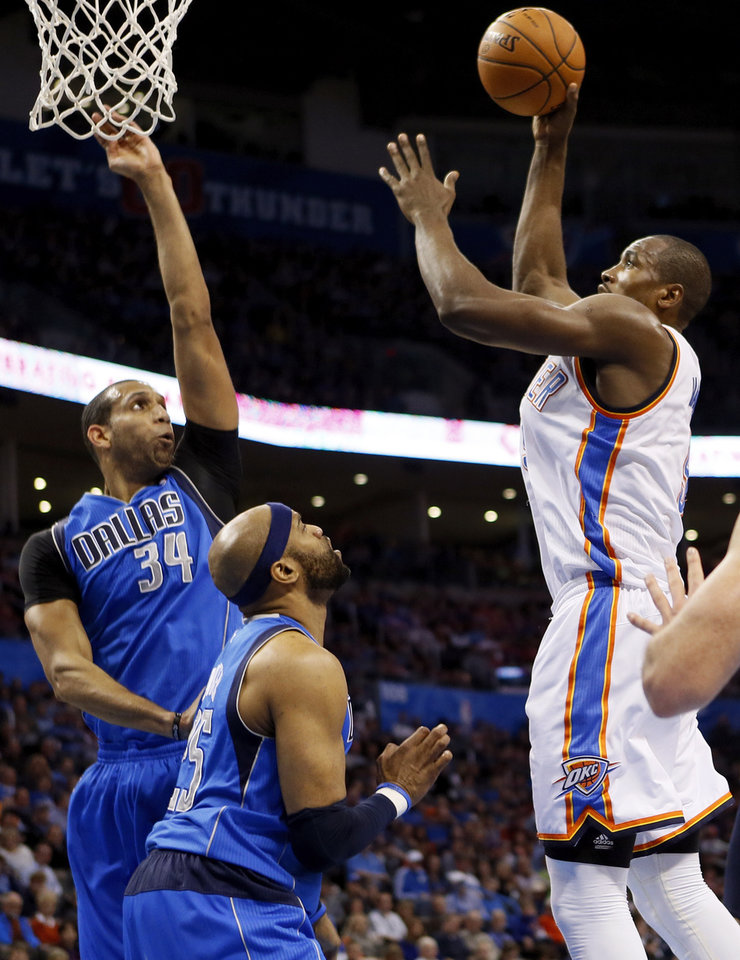 Photo - Oklahoma City's Serge Ibaka (9) shoots against Dallas' Brandan Wright (34) and Vince Carter (25) during an NBA basketball game between the Oklahoma City Thunder and the Dallas Mavericks at Chesapeake Energy Arena in Oklahoma City, Sunday, March 16, 2014. Photo by Nate Billings, The Oklahoman