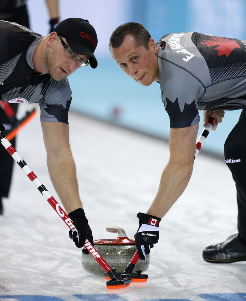 Photo - Canada's Brian Harndin, left, and E. J. Harnden sweep ahead of the rock during men's curling competition against Sweden the 2014 Winter Olympics, Tuesday, Feb. 11, 2014, in Sochi, Russia. (AP Photo/Robert F. Bukaty)