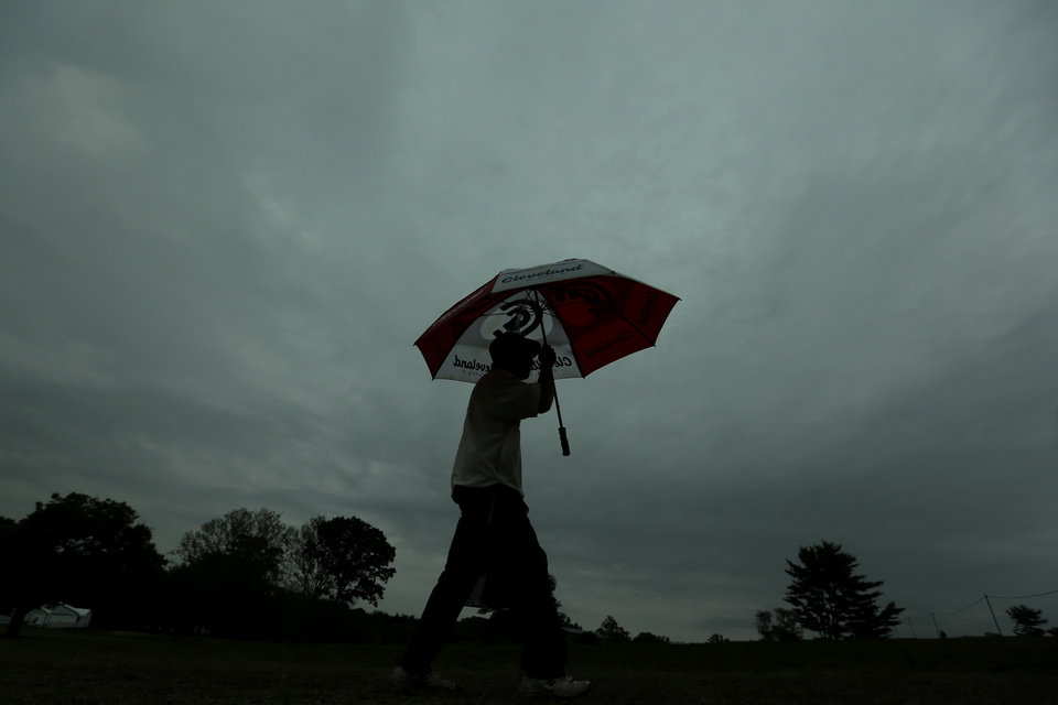 Photo - A spectator walks off the course as a weather warning delays the first round of the U.S. Open golf tournament at Merion Golf Club, Thursday, June 13, 2013, in Ardmore, Pa. (AP Photo/Charlie Riedel)