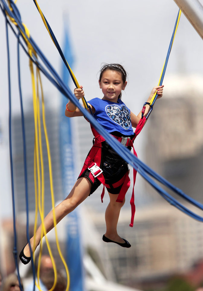 Photo -  Mailee Reavis, 9, Oklahoma City, is lifted high above the ground while swinging on the bungee ride June 29, 2013, at the Stars and Stripes Festival regatta on the Oklahoma River at the Boathouse District. Archive Photo by Jim Beckel, The Oklahoman   Jim Beckel -
