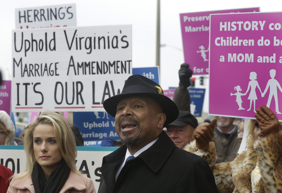 Photo - Former Republican lieutenant governor candidate E.W. Jackson, front center, speaks to the media during a demonstration outside Federal Court in Norfolk, Va., Tuesday, Feb. 4, 2014. Jackson spoke in favor of the law banning same-sex marriage. A federal judge will hear arguments Tuesday on whether Virginia's ban on gay marriage is unconstitutional. The state's newly elected Democratic attorney general has already decided to side with the plaintiffs and will not defend the ban.  (AP Photo/Steve Helber)