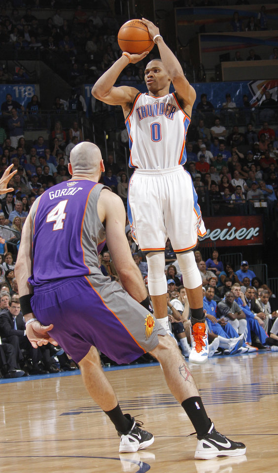 Oklahoma City Thunder point guard Russell Westbrook (0) puts up a shot over Phoenix Suns center Marcin Gortat (4) during the NBA basketball game between the Oklahoma City Thunder and the Phoenix Suns at the Chesapeake Energy Arena on Wednesday, March 7, 2012 in Oklahoma City, Okla.  Photo by Chris Landsberger, The Oklahoman