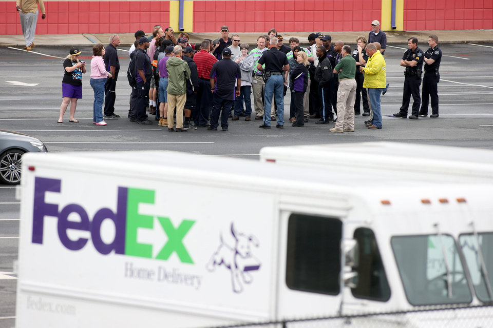 Photo - A police officer, center, talks with FedEx employees as they wait to meet their family at a nearby business after they were evacuated from the Airport Road FedEx facility after an early morning shooting Tuesday April 29, 2014, in Kennesaw, Ga. A shooter opened fire at a FedEx center wounding at least six people before police swarmed the facility. The shooter was found dead from an apparent self-inflicted gunshot wound. (AP Photo/Jason Getz)