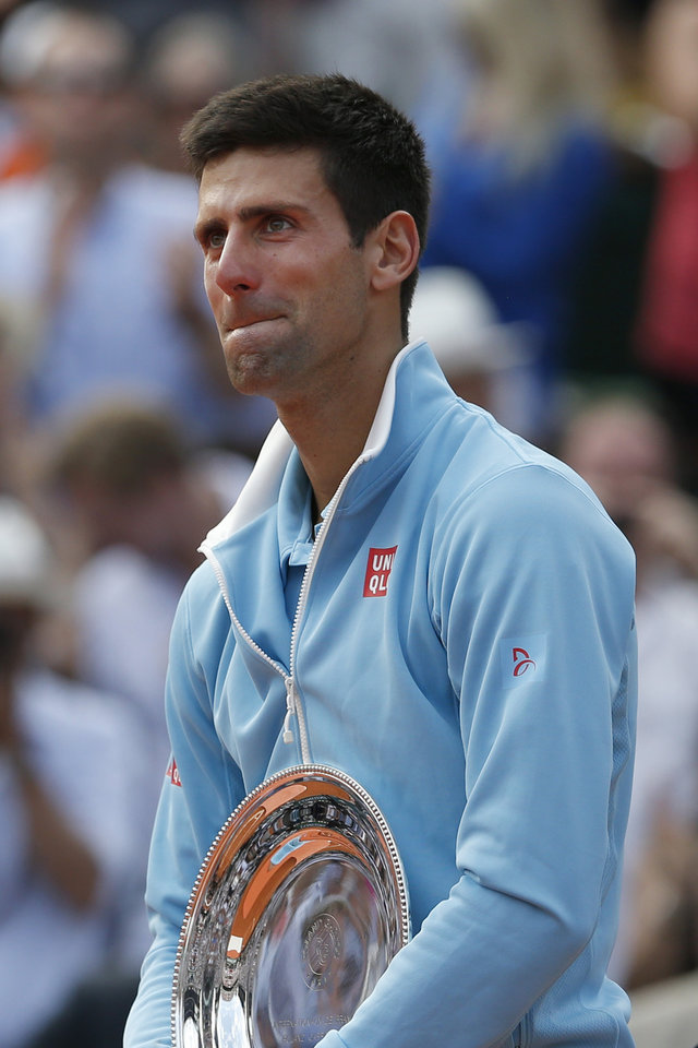 Photo - Serbia's Novak Djokovic holds the runner-up trophy after losing the final of the French Open tennis tournament against Spain's Rafael Nadal at the Roland Garros stadium, in Paris, France, Sunday, June 8, 2014. Nadal won in four sets 3-6, 7-5, 6-2, 6-4. (AP Photo/Darko Vojinovic)