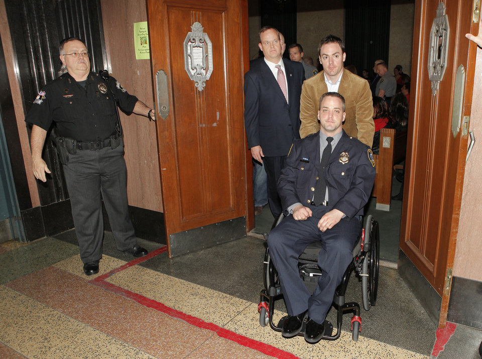Oklahoma City police officer Chad Peery  leaves a courtroom in a wheelchair Friday after testifying about his injuries at a sentencing for one of his assailants. His brother Mark Peery is pushing the wheelchair. Behind them is prosecutor Scott Rowland.  P