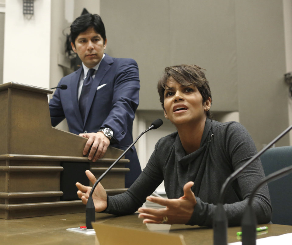 Photo - FILE - In this Aug. 13, 2013, file photo, actress Halle Berry urges lawmakers to support a bill that would limit the ability of paparazzi to photograph children of celebrities and public figures, at the Capitol in Sacramento, Calif. The bill, by state Sen. Kevin de Leon, D-Los Angeles, left, was approved by the Legislature and signed by Gov. Jerry Brown, is one of the more than 800 new laws to take effect Jan. 1. (AP Photo/Rich Pedroncelli, File)