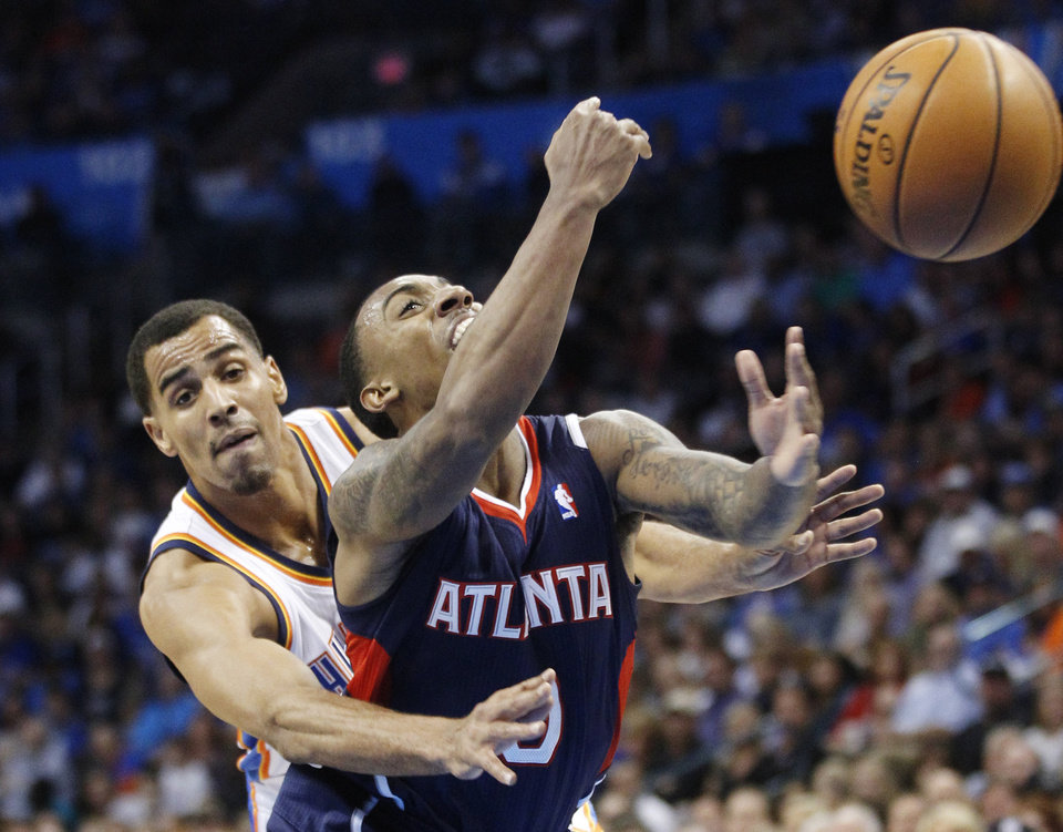 Atlanta Hawks guard Jeff Teague, right, is fouled by Oklahoma City Thunder guard Thabo Sefolosha, left, during the first quarter of an NBA basketball game in Oklahoma City, Sunday, Nov. 4, 2012. (AP Photo/Sue Ogrocki)