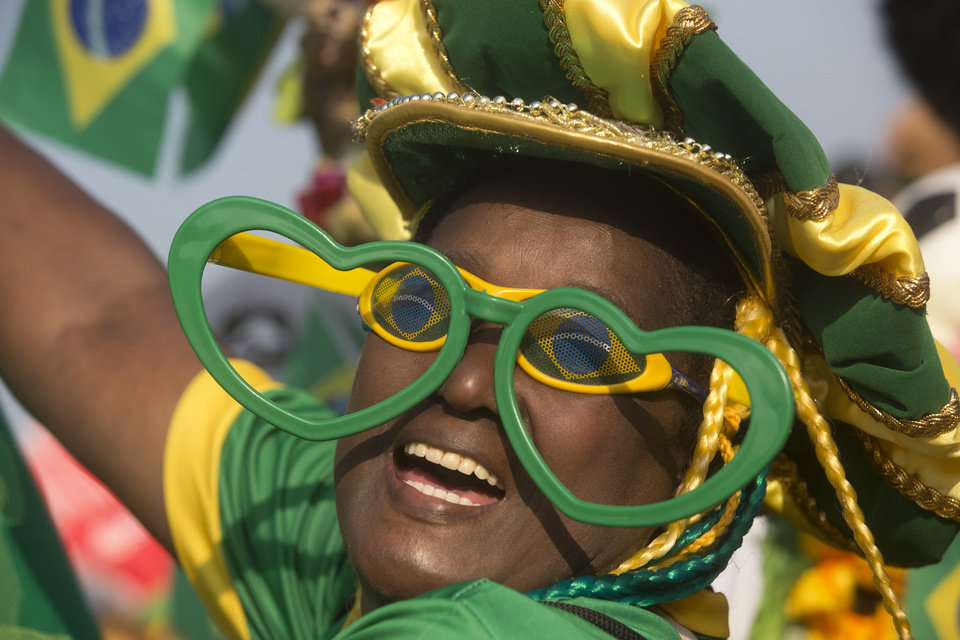 Photo - A Brazil soccer fan in costume cheers before the start of a live broadcast of a World Cup match between Brazil and Mexico inside the FIFA Fan Fest area on Copacabana beach, in Rio de Janeiro, Brazil, Tuesday, June 17, 2014. (AP Photo/Silvia Izquierdo)