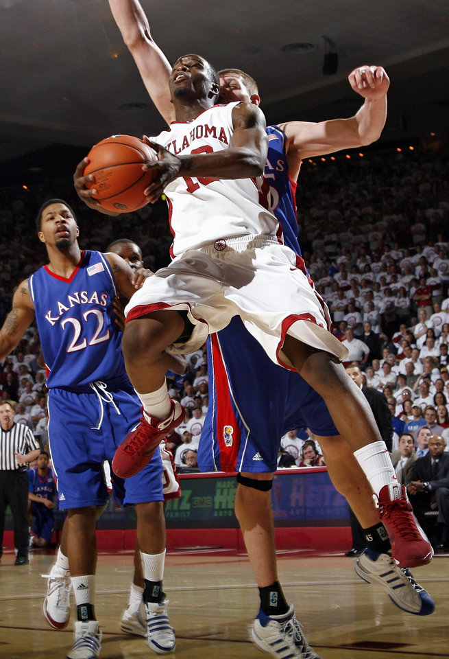 OU's Willie Warren (13) moves to the hoop in front of KU's Cole Aldrich (45) and Marcus Morris (22) in the second half of the men's college basketball game between Kansas and Oklahoma at the Lloyd Noble Center in Norman, Okla., Monday, February 23, 2009. KU won, 87-78. BY NATE BILLINGS, THE OKLAHOMAN