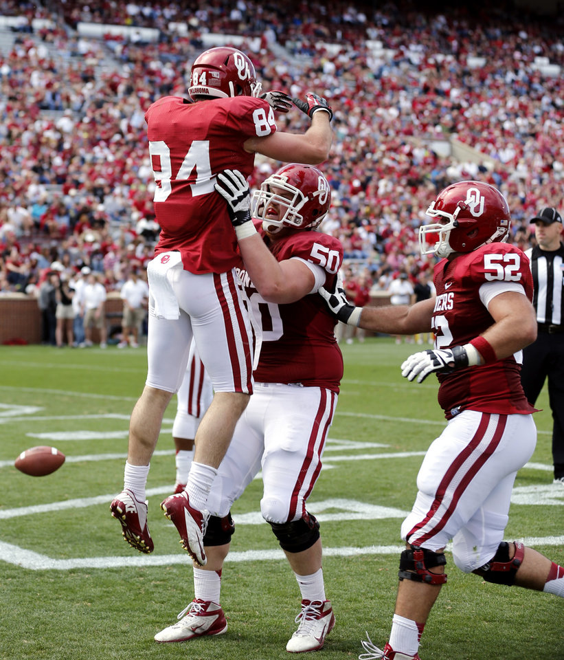Photo - Don Caudill (84) is lifted by Austin Woods (50) in celebration after a touchdown pass reception during the annual Spring Football Game at Gaylord Family-Oklahoma Memorial Stadium in Norman, Okla., on Saturday, April 13, 2013. Photo by Steve Sisney, The Oklahoman