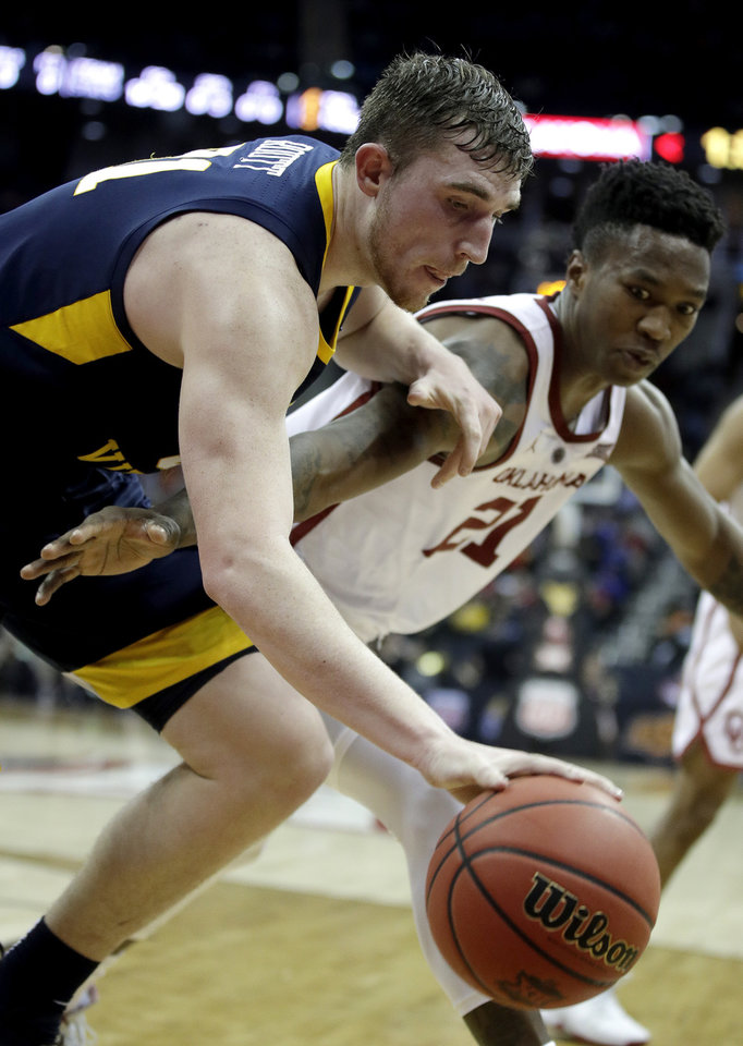 Photo - West Virginia's Logan Routt, left, and Oklahoma's Kristian Doolittle (21) chase the ball during the first half of an NCAA college basketball game in the Big 12 men's tournament Wednesday, March 13, 2019, in Kansas City, Mo. (AP Photo/Charlie Riedel)