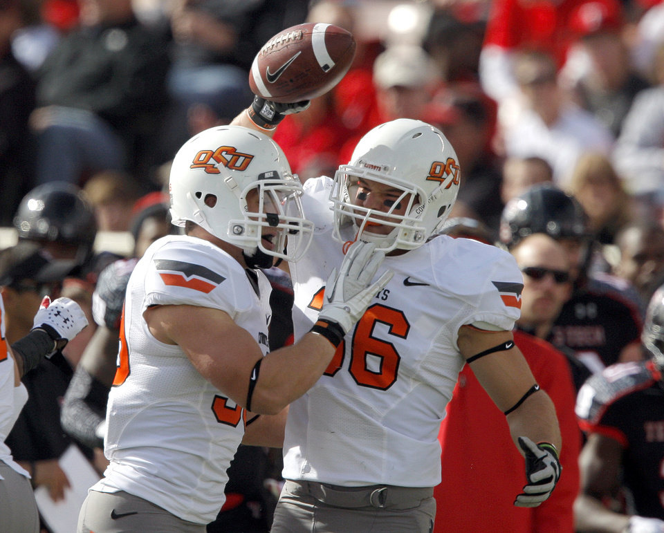 Oklahoma State\'s Kyle Hale (39) and Oklahoma State\'s Teddy Johnson (36) celebrate a OSU defensive play during a college football game between Texas Tech University (TTU) and Oklahoma State University (OSU) at Jones AT&T Stadium in Lubbock, Texas, Saturday, Nov. 12, 2011. Photo by Sarah Phipps, The Oklahoman ORG XMIT: KOD