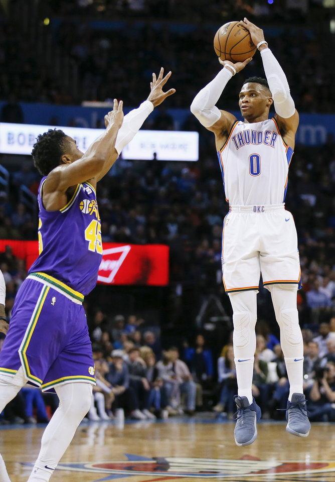 Photo - Oklahoma City's Russell Westbrook (0) shoots over Utah's Donovan Mitchell (45) during an NBA basketball game between the Utah Jazz and the Oklahoma City Thunder at Chesapeake Energy Arena in Oklahoma City, Monday, Dec. 10, 2018. Oklahoma City won 122-113. Photo by Nate Billings, The Oklahoman