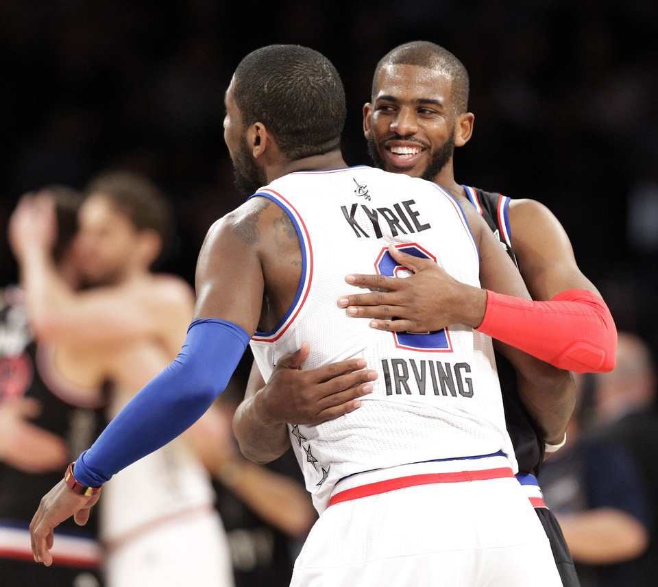 Photo - West Team's Chris Paul, right, of the Los Angeles Clippers, hugs East Team's Kyrie Irving, of the Cleveland Cavaliers, after the NBA All-Star basketball game, Sunday, Feb. 15, 2015, in New York. The West Team won 163-158. (AP Photo/Kathy Willens)
