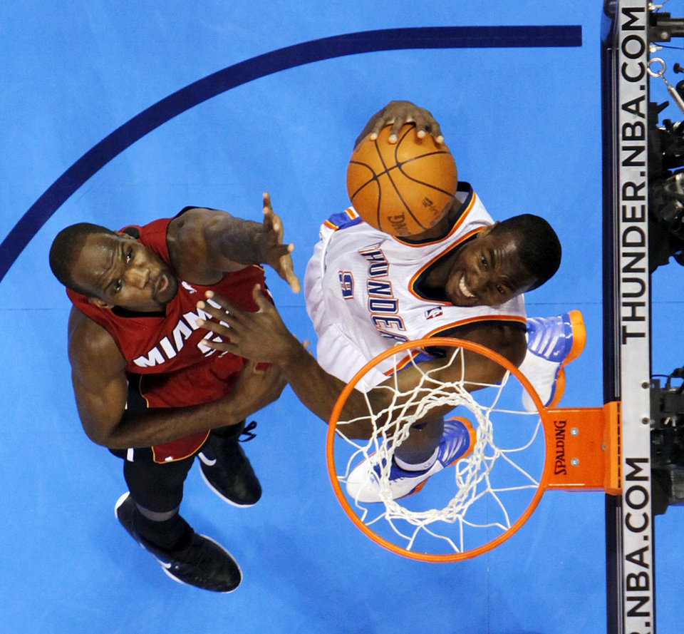 Oklahoma City's Serge Ibaka (9) dunks the ball past Miami's Joel Anthony (50) during the NBA basketball game between the Miami Heat and the Oklahoma City Thunder at Chesapeake Energy Arena in Oklahoma City, Sunday, March 25, 2012. Oklahoma City won, 103-87. Photo by Nate Billings, The Oklahoman