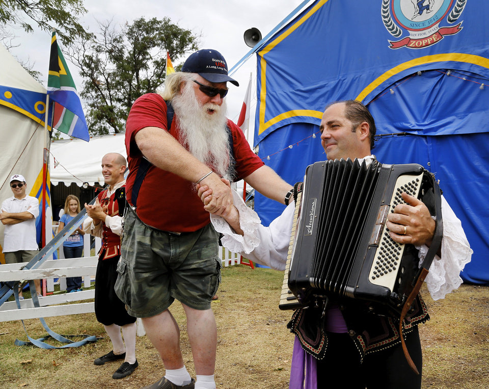 Photo - After requesting a member of the Zoppe Italian Family Circus to play a song on his accordion, Bob Moore of Piedmont, was pulled from the crowd and invited to stand on a drum to sing the song while accordionist Jay Walther provided the tune. When he finished, Moore shook the hand Walther's hand and thanked him for playing the song. After performing a few tunes to warm up the crowd, the curtains of the tent were opened and the circus performers entertained a crowd of about 500 fairgoers under the big top tent in the Centennial Plaza at the Oklahoma State Fair on Wednesday,  Sep. 18, 2013. Photo  by Jim Beckel, The Oklahoman.