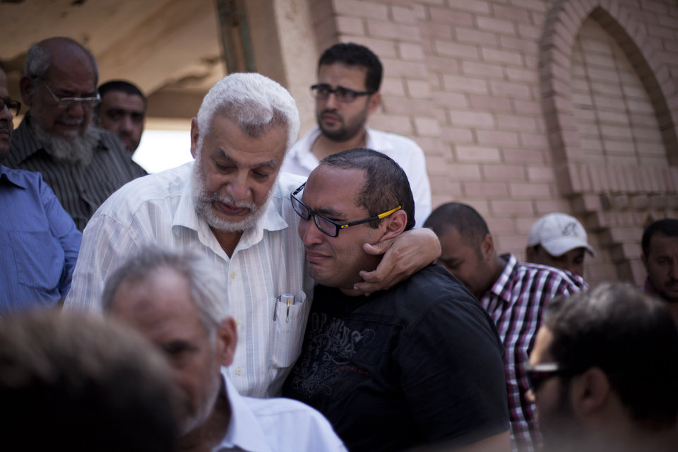 Photo - Friends of Ammar Badie, 38, killed Friday by Egyptian security forces during clashes in Ramses Square, and also son of Muslim Brotherhood's spiritual leader Mohammed Badie, comfort each other while attending his burial in Cairo's Katameya district, Egypt, Sunday, Aug. 18, 2013. Egypt increased security at the Supreme Constitutional Court building ahead of planned mass rallies by supporters of the country's ousted President Mohammed Morsi. (AP Photo/Manu Brabo)