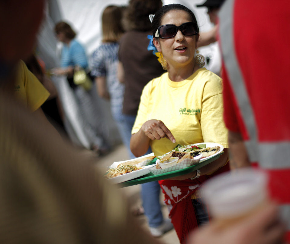 Photo - Shannon Primeau, director of Flamenco Fantastico, encourages visitors to try food from the Cafe do Brasil & Flamenco Fantasico of the Everything Goes Dance Studio booth on International Food Row during the Festival of the Arts in downtown Oklahoma City, Wednesday, April 25, 2012. Photo by Nate Billings, The Oklahoman