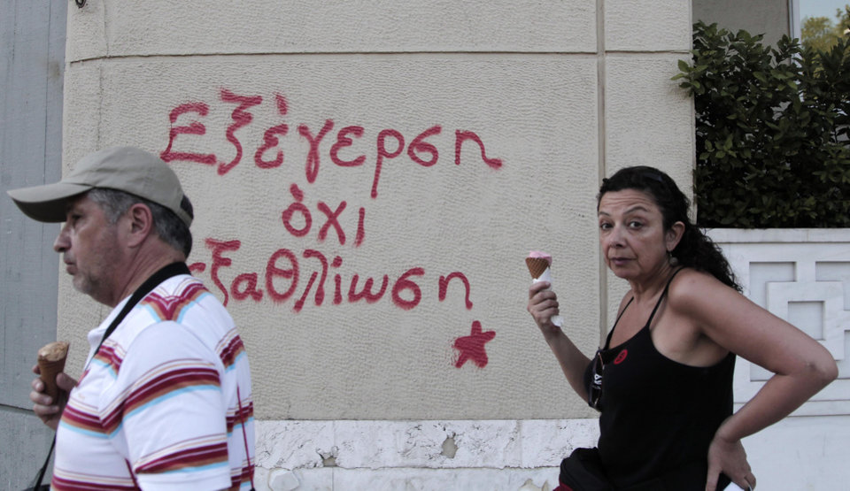 Photo -   Pedestrian holding ice creams walk in front of graffiti in Athens, Tuesday, Sept. 25, 2012. Unions have called a nationwide general strike Wednesday to protest new austerity measures being hammered out between the government and Greece's international creditors to ensure the country continues receiving emergency loans that have kept it afloat since 2010. Graffiti reads