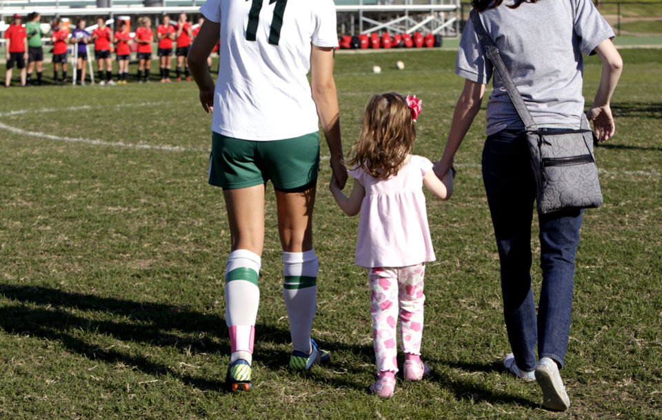 Bishop McGuinness soccer player Cierra Allen, left, walks with Chloe Hood, 4, of Good Shepherd Catholic School at Mercy. Photo by Sarah Phipps, The Oklahoman