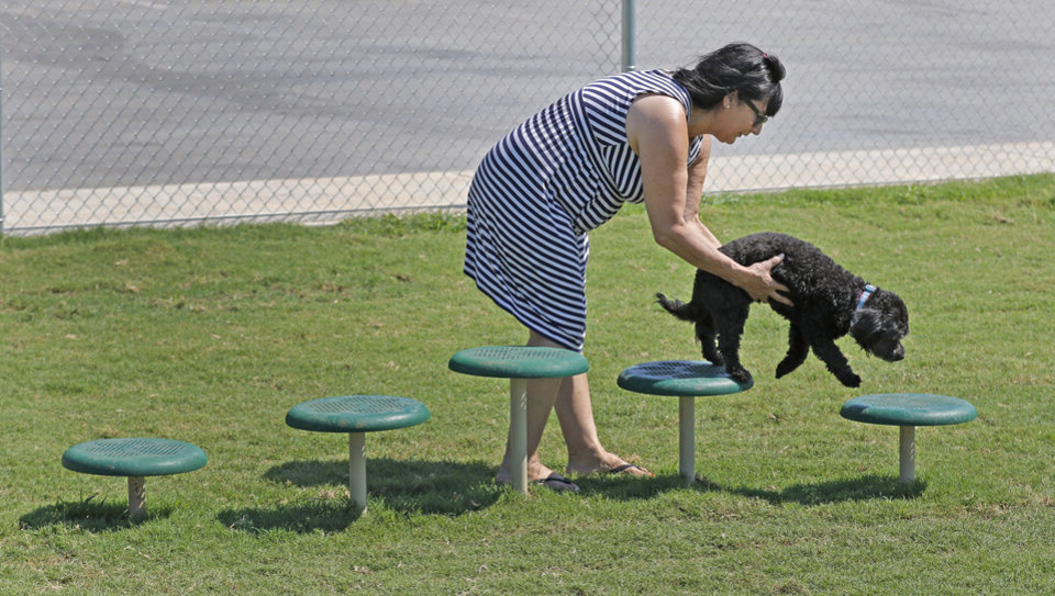 Photo -  Coco McBurney, of Upland, Calif., and her dog, Sadie, take a break from traveling Wednesday at the OnCue dog park in Yukon. [Photo By Steve Gooch, The Oklahoman]