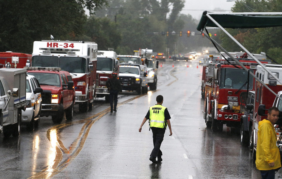 Photo - Rescue workers and vehicles stand parked waiting for roads to become passable following overnight flash flooding in Boulder, Colo., Thursday, Sept 12, 2013.  Heavy rains and scarring from recent wildfires sent walls of water crashing down mountainsides early Thursday in Colorado, cutting off mountain towns.  Boulder County was hit hardest, but flooding was reported all along the Front Range, from Colorado Springs to north of Fort Collins.(AP Photo/Brennan Linsley)