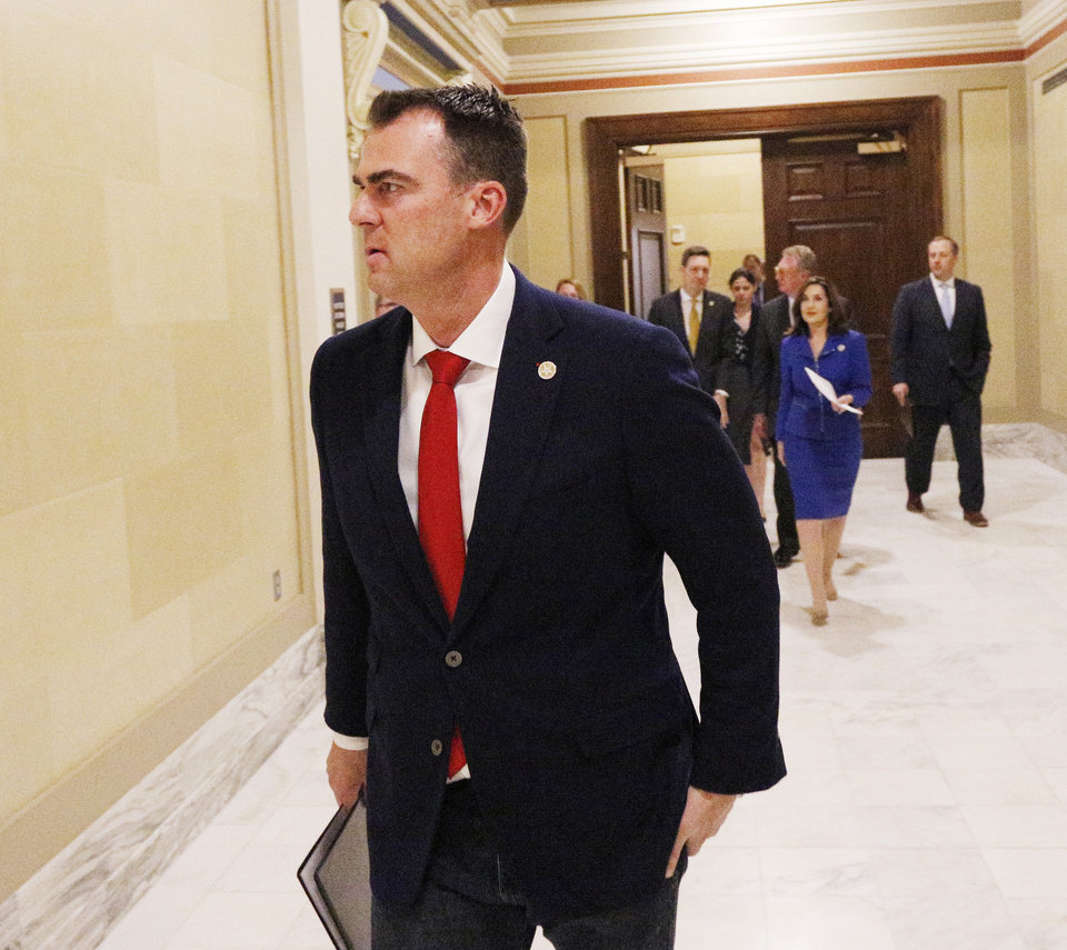 Photo - Gov. Kevin Stitt arrives at the Blue Room as Oklahoma government officials have a press conference to discuss the state's response to the Covid-19 Thursday, March 12, 2020.  [Photo by Doug Hoke/The Oklahoman]