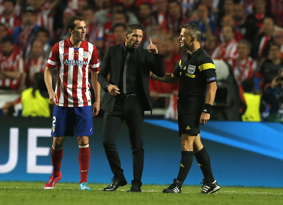 Photo - Atletico's coach Diego Simeone, centre, talks with referee Bjorn Kuipers, during the Champions League final soccer match between Atletico Madrid and Real Madrid in Lisbon, Portugal, Saturday, May 24, 2014. (AP Photo/Andres Kudacki)