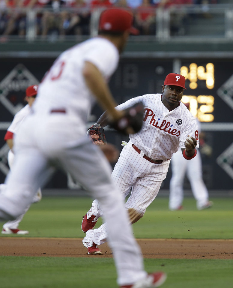 Photo - Philadelphia Phillies' Ryan Howard tosses the ball to pitcher Cole Hamels for an out at first on Miami Marlins' Tom Koehler in the third inning of a baseball game, Thursday, June 26, 2014, in Philadelphia. (AP Photo/Laurence Kesterson)