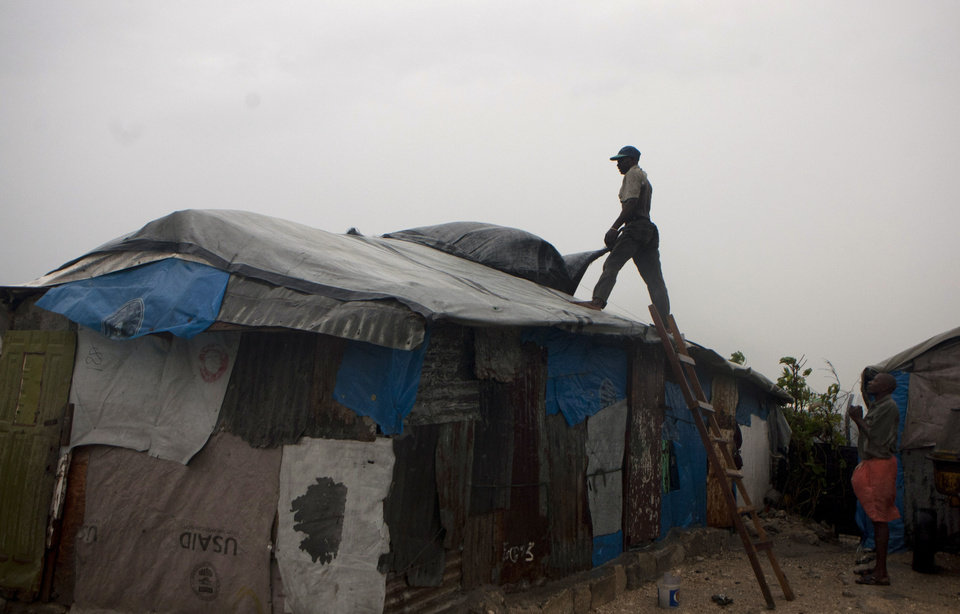 Photo -   A man works to repair the roof of his tent in a camp for people displaced by the 2010 earthquake as Tropical Storm Isaac affects Port-au-Prince, Haiti, Saturday, Aug. 25, 2012. Tropical Storm Isaac swept across Haiti's southern peninsula early Saturday, dousing a capital city prone to flooding and adding to the misery of a poor nation still trying to recover from the 2010 earthquake. (AP Photo/Dieu Nalio Chery)