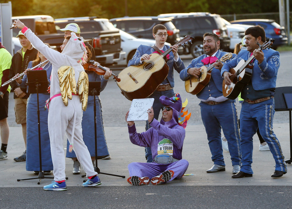 Photo - Dressed as unicorns, Leslie Driskill, left, and David Bach take a selfie with a mariachi band at a water stop across the street from Little Flower Church on S Walker Ave. during the Oklahoma City Memorial Marathon in Oklahoma City, Sunday, April 28, 2019. [Nate Billings/The Oklahoman]