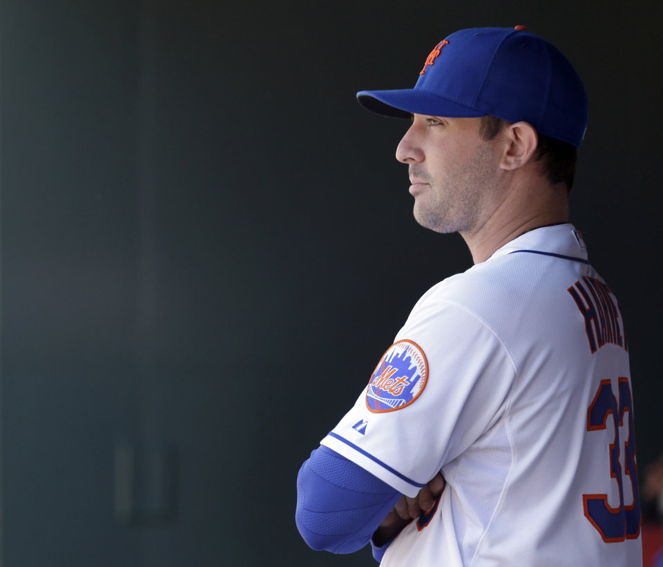 Photo - FILE - In this April 6, 2014 file photo, New York Mets starting pitcher Matt Harvey stands in the dugout before a baseball game against the Cincinnati Reds at Citi Field in New York. More than a dozen major league pitchers have needed Tommy John surgery this year, a group that includes All-Stars Patrick Corbin, Josh Johnson and Matt Moore, joining an illustrious group that includes Chris Carpenter (2007), Stephen Strasburg (2010), Adam Wainwright (2011) and Matt Harvey (2013). (AP Photo/Seth Wenig, File)