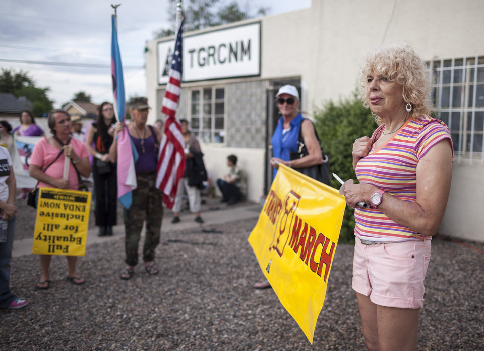 Photo - In this May 29, 2014 photo, Denee Mallon, right, holds a banner before taking part in the Trans March to Morningside Park in Albuquerque, N.M. A U.S. Department of Health and Services review board ruled Friday, May 30, in favor of Mallon, a 74-year-old Army veteran, whose request to have Medicare pay for her genital reconstruction was denied two years ago. The decision recognizes sex reassignment surgeries as a medically necessary and effective treatment for individuals who do not identify with their biological sex. (AP Photo/Craig Fritz)