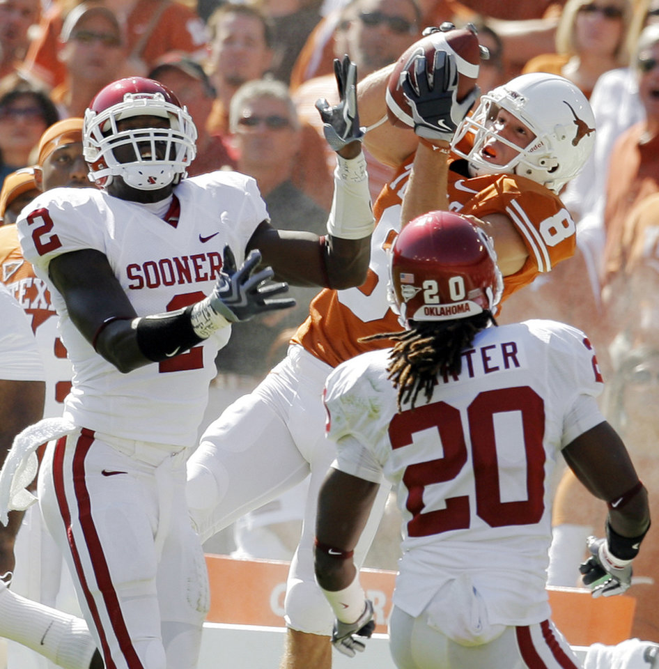 Photo - Jordan Shipley (8) of Texas tries to make a catch between OU's Brian Jackson (2) and Quinton Carter (20) during the Red River Rivalry college football game between the University of Oklahoma Sooners (OU) and the University of Texas Longhorns (UT) at the Cotton Bowl in Dallas, Texas, Saturday, Oct. 17, 2009. OU was called for defensive pass interference on the play. Photo by Nate Billings, The Oklahoman