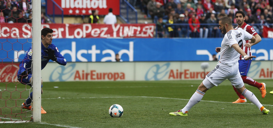 Photo - Real's Karim Benzema, second right, scores a goal past Atletico's goalkeeper Thibaut Courtois, left, during a Spanish La Liga soccer match between Atletico de Madrid and Real Madrid at the Vicente Calderon stadium in Madrid, Spain, Sunday, March 2, 2014. (AP Photo/Andres Kudacki)
