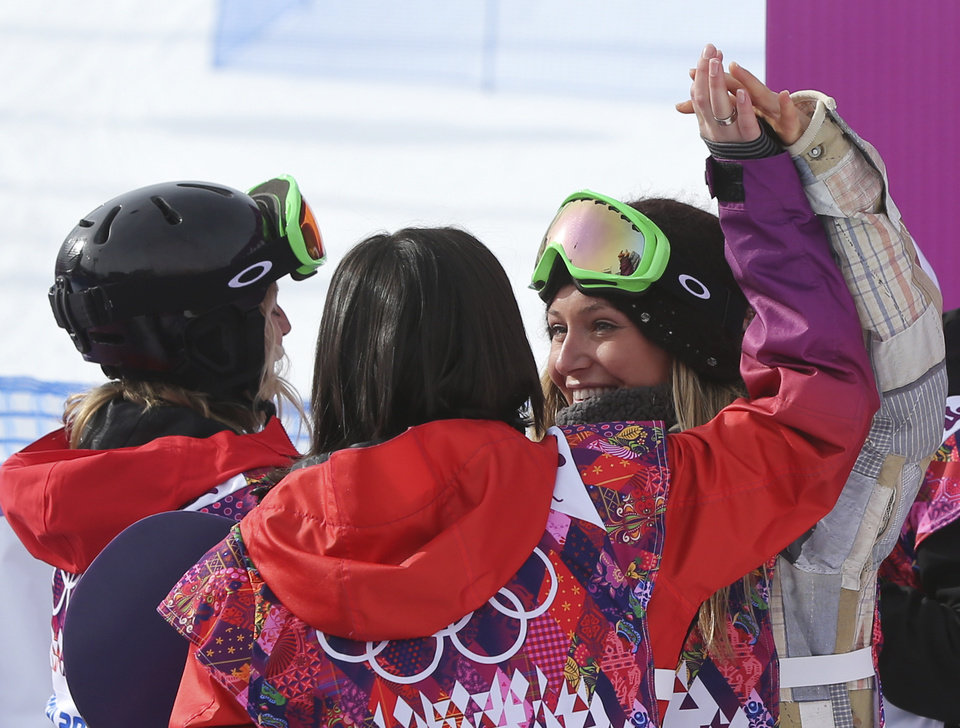 Photo - Jamie Anderson of the United States, right celebrates with Switzerland's Sina Candrian, center, and Britain's Jenny Jones, left, after Anderson won the women's snowboard slopestyle final at the 2014 Winter Olympics, Sunday, Feb. 9, 2014, in Krasnaya Polyana, Russia. (AP Photo/Sergei Grits)