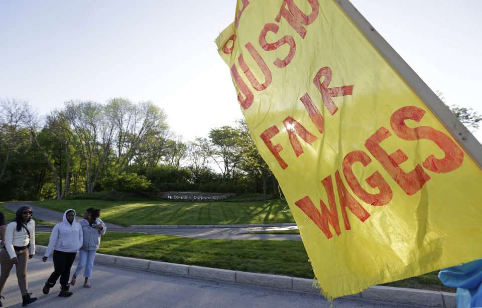 Photo - A McDonalds sign can be seen in the background as hundreds of demonstrators begin gather outside the entrance of the McDonalds Corporation, Thursday, May 22, 2014, in Oak Brook, Ill., protesting for a $15 an hour wage and the right to unionize. The group gathered outside the entrance as the company held the annual shareholders meeting. (AP Photo/M. Spencer Green)