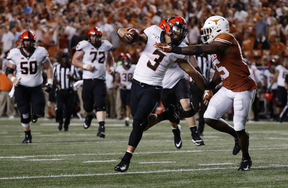 Photo - Oklahoma State quarterback Spencer Sanders (3) is hit by Texas defensive back Chris Brown (15) on a run during the second half of an NCAA college football game Saturday, Sept. 21, 2019, in Austin, Texas. (AP Photo/Eric Gay)