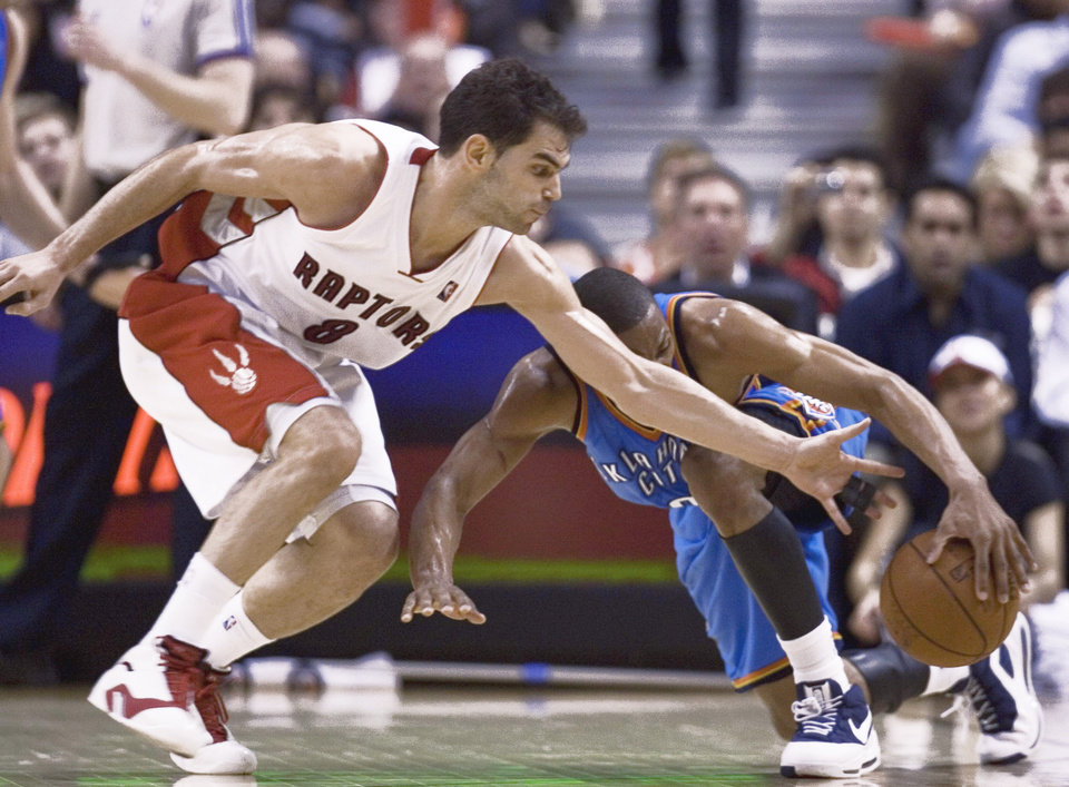 Photo - Toronto's Jose Calderon, left, tries to take the ball from Thunder guard Russell Westbrook during Oklahoma City's 112-96 loss Friday at the Air Canada Centre. Ap photo