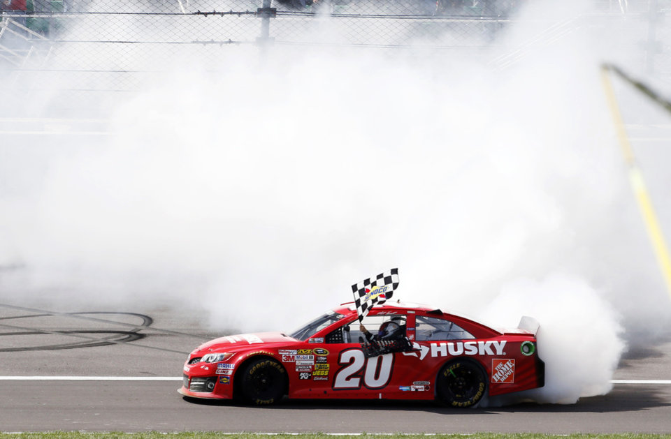 Photo - Matt Kenseth (20) performs a burnout after winning the NASCAR Sprint Cup Series auto race at Kansas Speedway in Kansas City, Kan., Sunday, April 21, 2013. (AP Photo/Orlin Wagner)