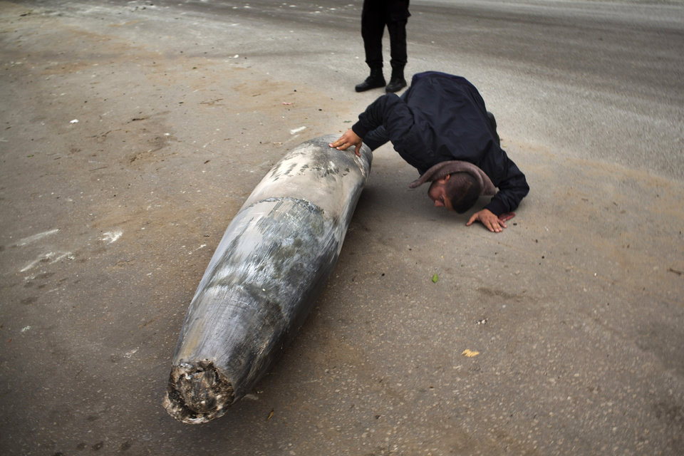 Photo -   A Hamas officer inspects an unexploded Israeli bomb in Gaza City, Saturday, Nov. 17, 2012. Israel bombarded the Hamas-ruled Gaza Strip with more than 180 airstrikes early Saturday, the military said, widening a blistering assault on militant operations to include the prime minister's headquarters, a police compound and a vast network of smuggling tunnels. The new attacks followed an unprecedented rocket strike aimed at the contested holy city of Jerusalem that raised the stakes in Israel's violent confrontation with Palestinian militants. (AP Photo/Bernat Armangue)