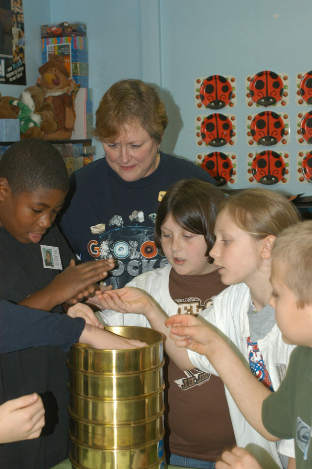Rose State College Dean of Engineering and Sciences, Jamie Graham, assists Del City Elementary students separate sedimentary samples. The Dare to Dream Team provides hands on classroom demonstrations to students in area schools<br/><b>Community Photo By:</b> Steve Reeves<br/><b>Submitted By:</b> Donna, Choctaw