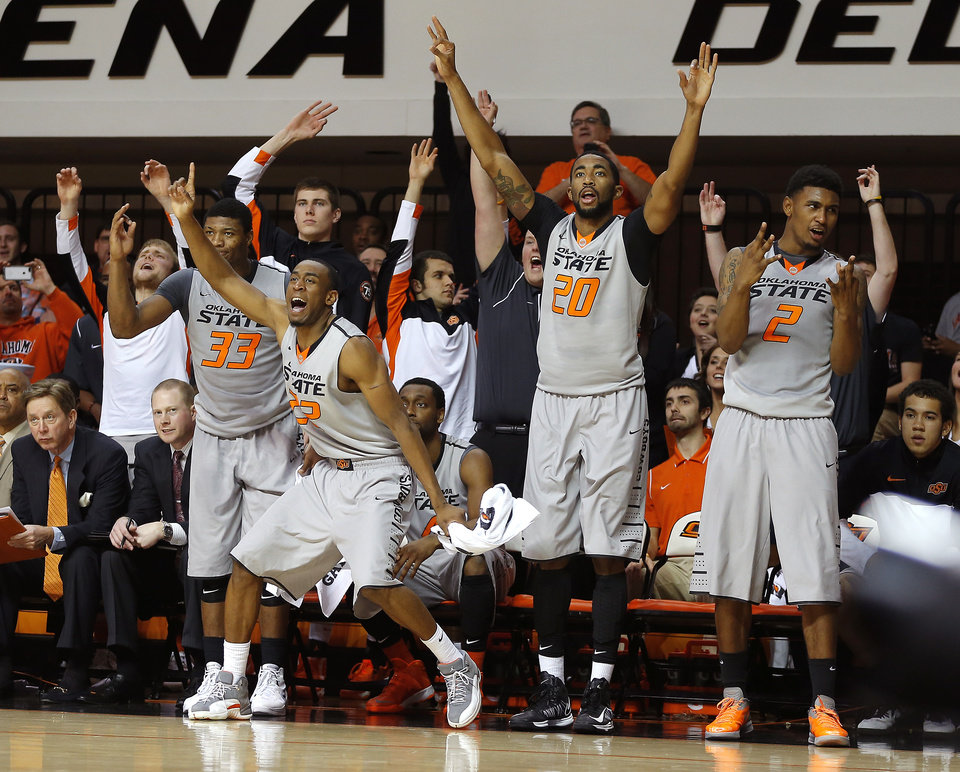 Photo - Oklahoma State's Marcus Smart (33), Markel Brown (22), Michael Cobbins (20), and Le'Bryan Nash (2) celebrate during an NCAA college basketball between Oklahoma State University and Delaware State at Gallagher-Iba Arena in Stillwater, Okla., Tuesday, December 17, 2013. Oklahoma State won 75-43. Photo by Bryan Terry, The Oklahoman