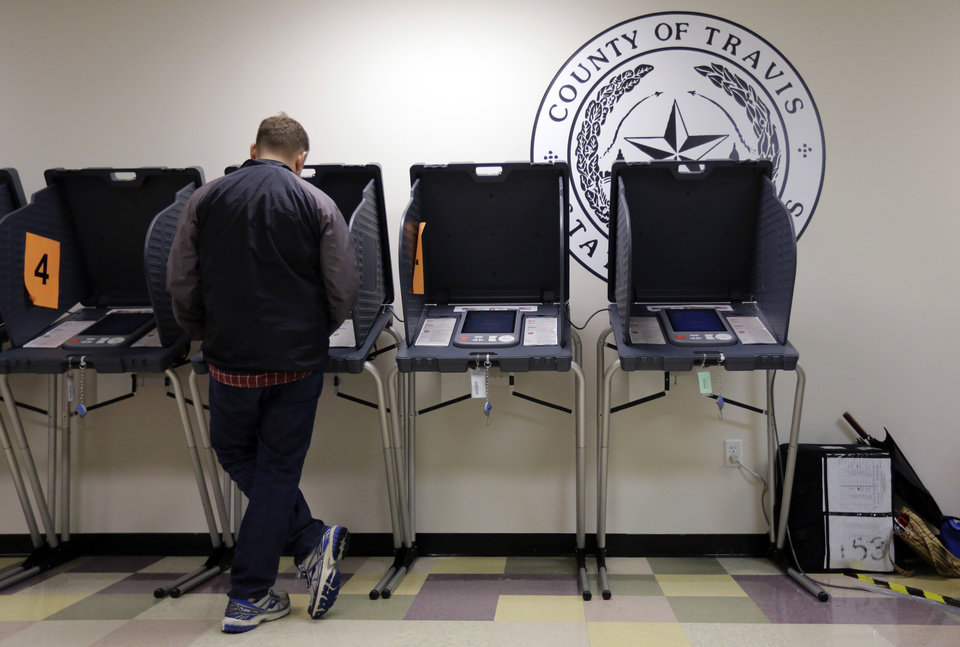 Photo - In this Wednesday, Feb. 26, 2014 photo, a voter casts his ballot at an early voting polling site, in Austin, Texas. In elections that begin next week, voters in 10 states will be required to present photo identification before casting ballots _ the first major test of voter ID laws after years of legal challenges arguing that the measures are designed to suppress voting. (AP Photo/Eric Gay)