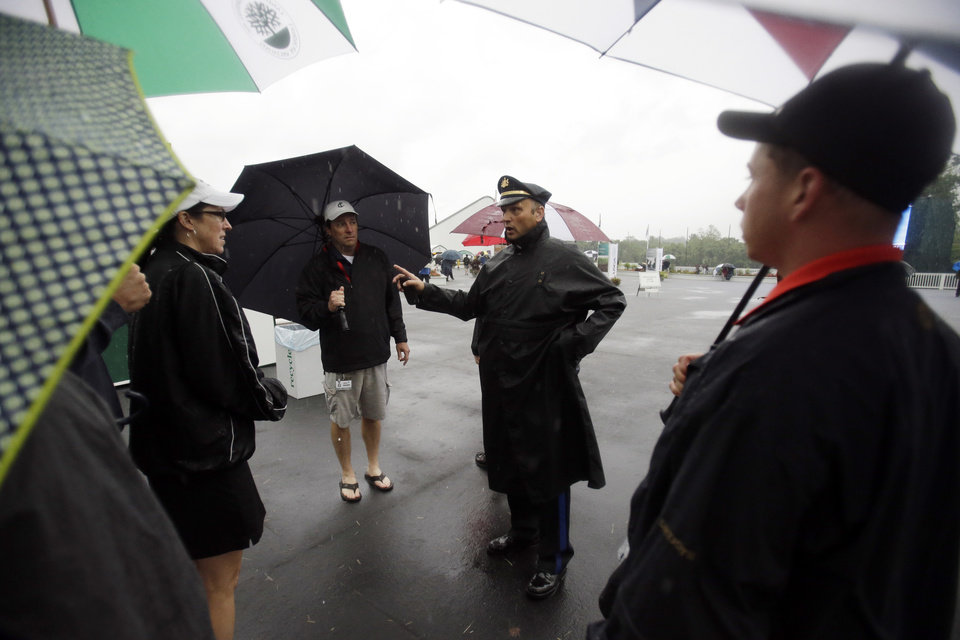 Photo - A police officer directs spectators off the course as weather delays the first round of the U.S. Open golf tournament at Merion Golf Club, Thursday, June 13, 2013, in Ardmore, Pa. (AP Photo/Gene J. Puskar)