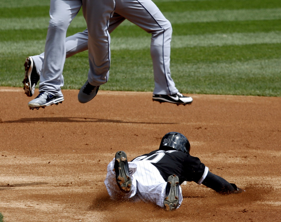 Photo - Chicago White Sox's Alejandro De Aza (30) steals second as Cleveland Indians second baseman Jason Kipnis, left, catches a high throw from Lou Marson, as shortstop Mike Aviles, background, runs behind during the first inning of a baseball game Wednesday, April 24, 2013, in Chicago. (AP Photo/Charles Rex Arbogast)