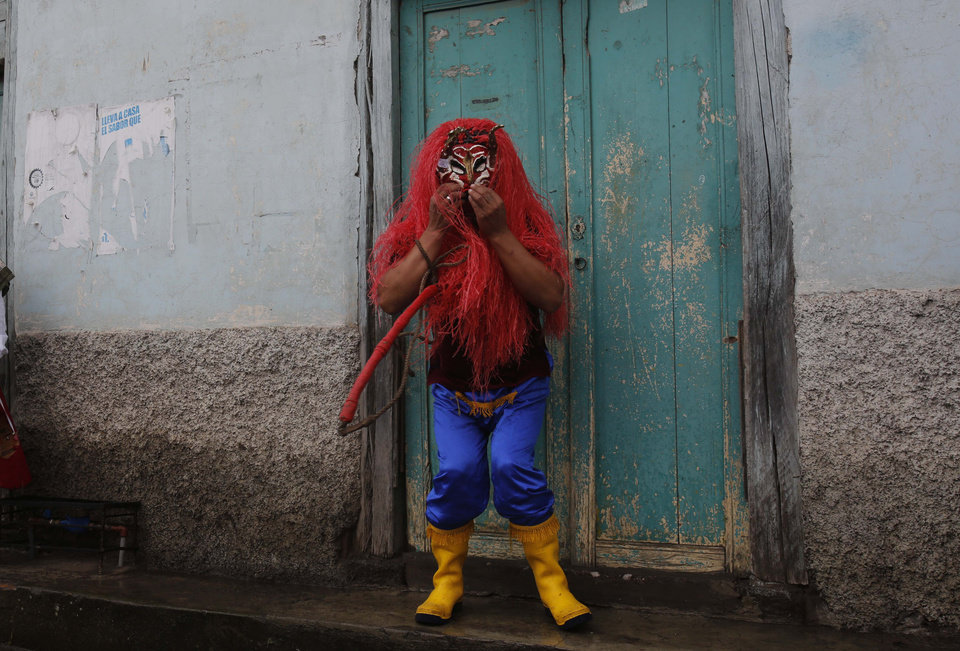 Photo - A man dressed up as the devil participates in La Diablada in Pillaro, Ecuador, Monday, Jan. 6, 2014. The feast celebrates the end of the year and start the new one. The town of Pillaro kicks off the feast of the La Diablada with neighborhoods competing to bring as many people dressed as different characters. Originally the devil costume was used to open up space to allow other participants to dance, but over the years the character gained popularity and became the soul of the feast. (AP Photo/Dolores Ochoa)