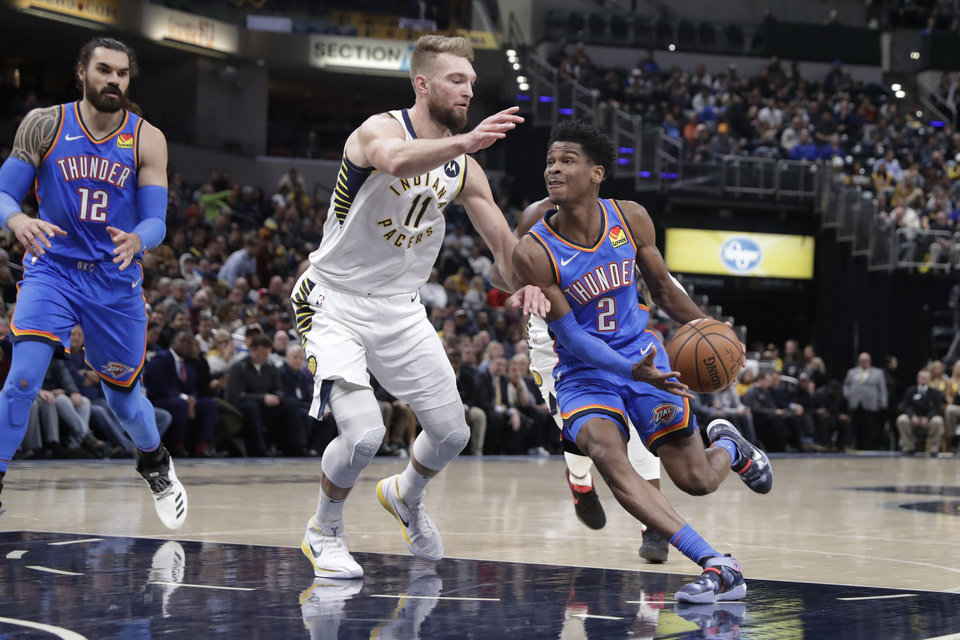 Photo - Oklahoma City Thunder guard Shai Gilgeous-Alexander (2) drives on Indiana Pacers forward Domantas Sabonis (11) during the first half of an NBA basketball game in Indianapolis, Tuesday, Nov. 12, 2019. (AP Photo/Michael Conroy)