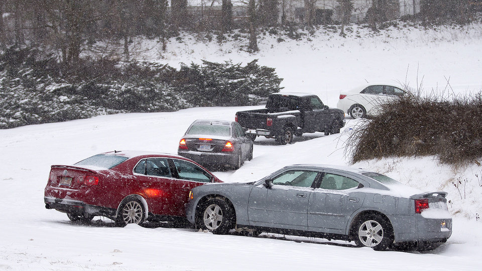 Photo - Cars that lost traction sit on the eastbound ramp from Joseph Bryan Boulevard to Holden Road during a snowfall in Greensboro, N.C., Wednesday, Feb. 12, 2014. A major winter slammed into North Carolina Wednesday, turning homebound commutes that typically take minutes into hours-long ordeals as traffic slowed to a slippery slog and threatening to leave many areas dark because of power outages. (AP Photo/News & Record, Nelson Kepley)